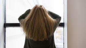 Person står vid ett fönster, tittar ut och håller händerna på huvudet.