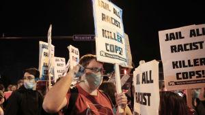 Man som bär munskydd håller upp skylt med budskapet ''fängsla alla mördarpoliser'' under demonstration i USA.