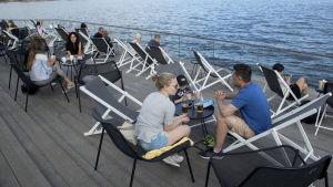 Personer sitter på en uteservering i Helsingfors. I bakgrunden syns hav.