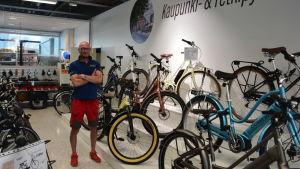 Medelålders man med rakat hår, kortärmad tröja och röda shorts står med armarna i kors i cykelaffär.