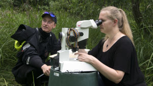 en man och en kvinna. Kvinnan tittar in i ett mikroskop och mannen har våtdräkt.