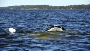 En liten del av en sjunkande båt syns ovanför vattenytan.