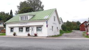 En vit träbyggnad med grönt tak i Ingå kyrkby som kallas laserhuset.