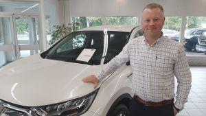 Man i vit skjorta som håller handen på en ny vit bil.