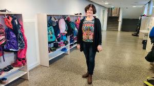 En kvinna står i en tom skolkorridor.