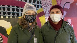 Emilia och Timo står med munskydd framför en färgglad vägg