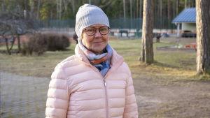 En kvinna med mössa och rosa, tunn vinterjacka står ute. Bakom tennisbana och klubbhus.
