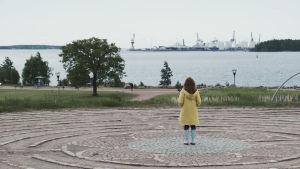 Keltaiseen takkiin ja kumisaappaisiin pukeutunut nainen seisoo puistolabyrintin keskikohdassa katsoen kohti merta. Taustalla konttisatama.
