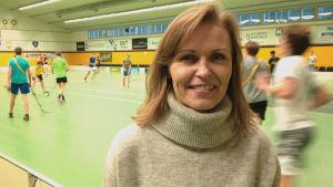 Lena Törnqvist står inne i Aurorahallen, med innebandyspelare i bakgrunden