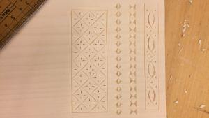 En ljus träskiva som dekorerats med grafiska mönster i träsnitt.