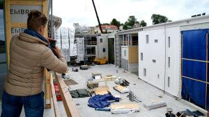 En kvinna i en beige dunrock tar en bild från en balkong över en byggarbetsplats.