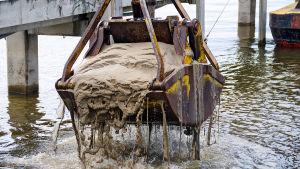 En grävskopa som lyfter upp muddermassor.