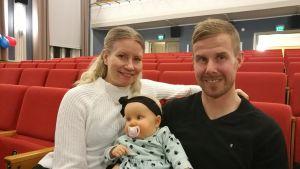 En kvinna och en man sitter med en bebis i famnen.