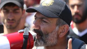 Den armeniska oppositionsledaren Nikol Pasjinian talar till demonstranter i Jerevan.