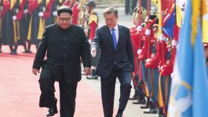 Nordkoreas ledare Kim Jong-Un och Sydkoreas president Moon Jae-In i Panmunjom då de stiger in i Fredshuset för att inleda förhandlingarna.