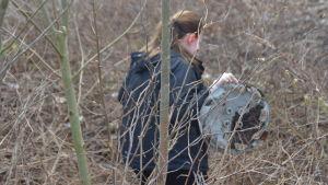 person med metallföremål i buskage