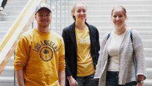 Gymnasieeleverna Eero Tihtonen, Annika Kantokorpi och Carolina Savander står vid trapporna inne i Gymnasiet Lärkan.