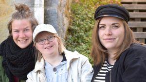 Emma Kullberg, Janina Egger och Emilia nyberg sitter på en trappa. Omkring trappan växer det gröna slingerväxter.