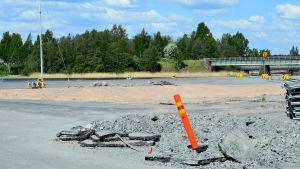 En sandgrop och en varningsstolpe i Norra hamnen i Ekenäs där hamnmagasinet stod tidigare. Hav i bakgrunden. En vacker sommardag.