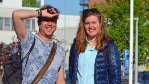 Larrie Griffis har armen höjd för atgt skydda sig mot solen, Karolina Lång kisar in i kameran.