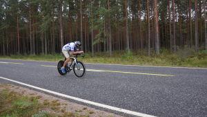 En cyklist susar fram på en landsväg.