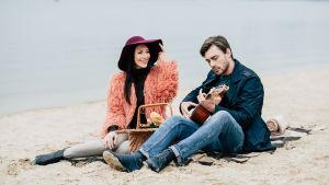 Kvinna och man sitter på en sandstrand, han spelar gitarr