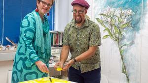 Kuvataiteilija Tero Annanolli seuraa toimittaja Lisa Enckellin viivan maalausta.