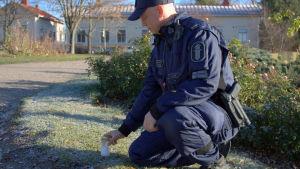 Seppo Ijäs ställer ett gravljus på marken.