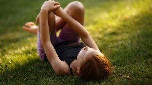 Flicka ligger i gräset