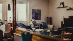 Carolina Sinisalo sitter i soffan och på väggen ovanför henne finns en stor bild av sonen Robin.
