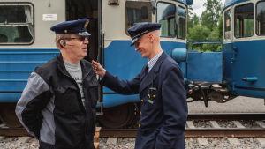 Kaksi miestä seisoo kahden sinisen junavaunun edessä, toisella vanha konduktöörinlakki päässä, toisella vanha junankuljettajan puku ja lakki.