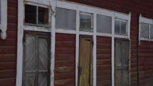 Förrådsbyggnader, rödmyllade trälider med söndriga fönster och sneda dörrar.