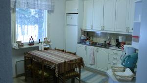 Ett kök med vit köksinredning. Ett bord med fem stolar runt står mitt i köket.
