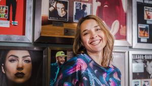 Laulaja Iisa hymyilee kameralle kultalevyseinän edessä, kuva rajattu rintakehästä ylöspäin.