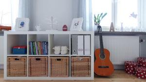 Bokhylla och gitarr i vardagsrum.