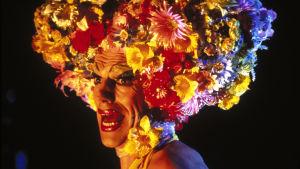 Hugo Weavingin näyttelemä drag queen lähikuvassa, täydessä loistossaan. Kuva elokuvasta Priscilla, aavikon kuningatar.