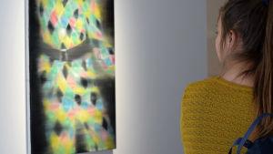 kvinna tittar på tavla på utställning