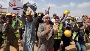 """Byggnadsarbetare tågade till en vallokal i den """"nya huvudstaden"""" som är under uppbyggnad i öknen öster om Kairo."""