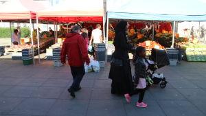 Kvinna med huvudduk promenerar med sina barn på torg med grönskasförsäljning i Tensta.