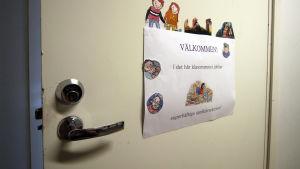 """En klassrumsdörr med en lapp där det står """"Välkommen - i det ähr klassrummet jobbar superhäftiga språkdetektiver."""""""