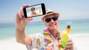 äldre man med solhatt tar en selfie på stranden, har en drink i handen.