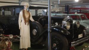 En stilig skyltdocka med minkkrage står bredvid en gammal bil i Geta nostalgi och motormuseum
