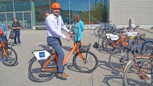 Man på orange cykel.