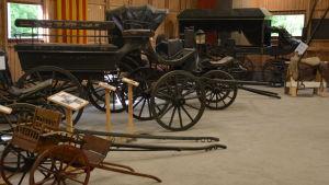 Gamla vagnar och skrindor  i ett museum. I bakgrunden också en gammal likvagn.