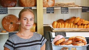 Kvinna står i ett bageri omringad av färska bullar och bröd.
