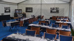 Festivaltält med dukade bord.