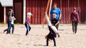 Barn leker på en sandstrand.