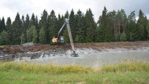 En grävmaskin gräver en sedimenteringsbassäng på en åker. Blivande våtmark