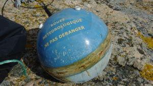 En boj på en sten. På bojen står det på franska att det är meteorologisk boj.