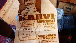 brunvit affisch med leende äldre dam med kaffekopp om kaffelotteri från 1945